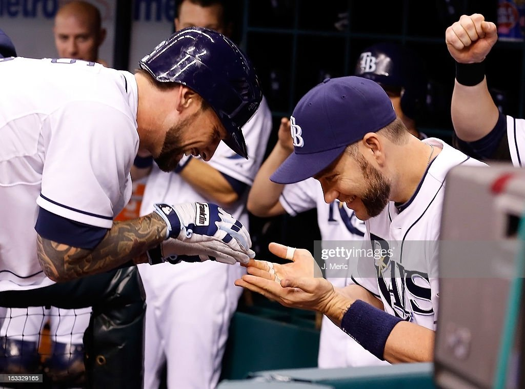 Designated hitter <a gi-track='captionPersonalityLinkClicked' href=/galleries/search?phrase=Luke+Scott&family=editorial&specificpeople=757156 ng-click='$event.stopPropagation()'>Luke Scott</a> #30 (right) of the Tampa Bay Rays congratulates Ryan Roberts #19 after his home run against the Baltimore Orioles during the game at Tropicana Field on October 3, 2012 in St. Petersburg, Florida.
