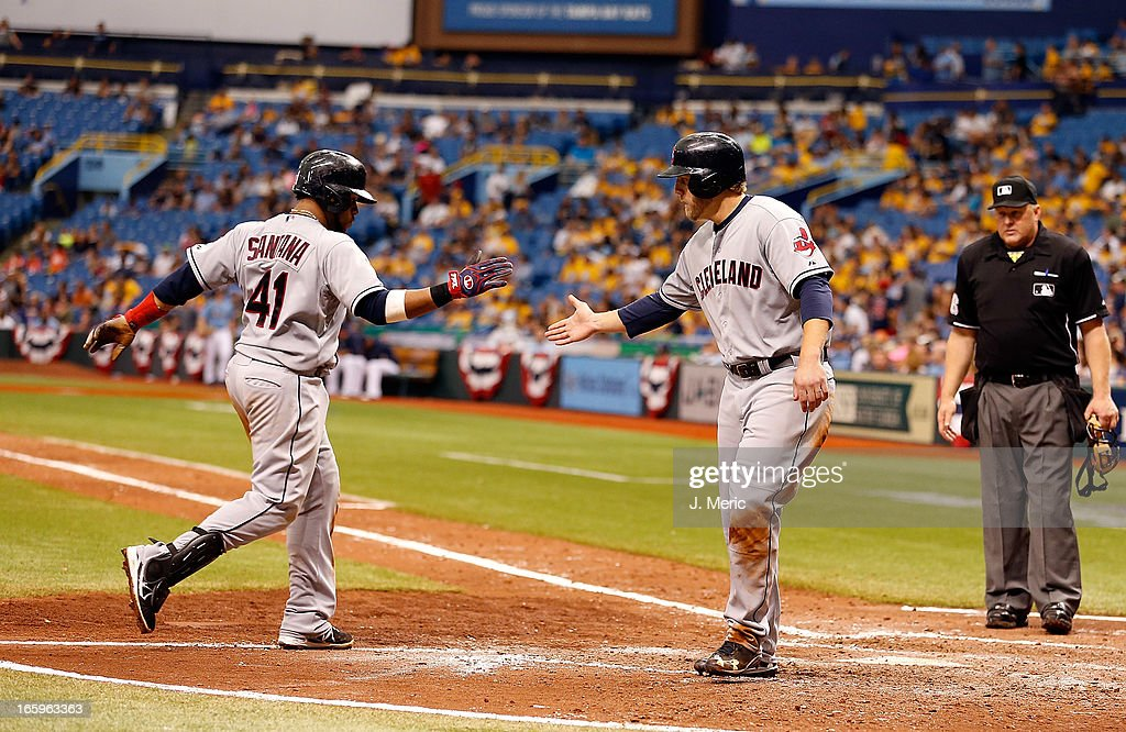Designated hitter Mark Reynolds #12 (right) of the Cleveland Indians congratulates catcher Carlos Santana #41 after his ninth inning home run against the Tampa Bay Rays during the game at Tropicana Field on April 7, 2013 in St. Petersburg, Florida.