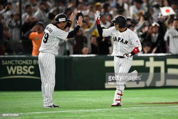Designated hitter Tetsuto Yamada of Japan celebrates with coach Takayuki Onishi after hittin a two run homer to make it 58 in the bottom of the...