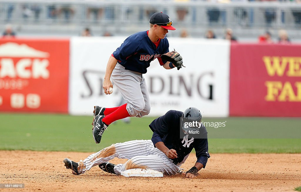 Designated hitter Thomas Neal #60 of the New York Yankees is out at second as infielder Brock Holt #26 of the Boston Red Sox jumps to avoid him during a Grapefruit League Spring Training Game at George M. Steinbrenner Field on March 20, 2013 in Tampa, Florida.