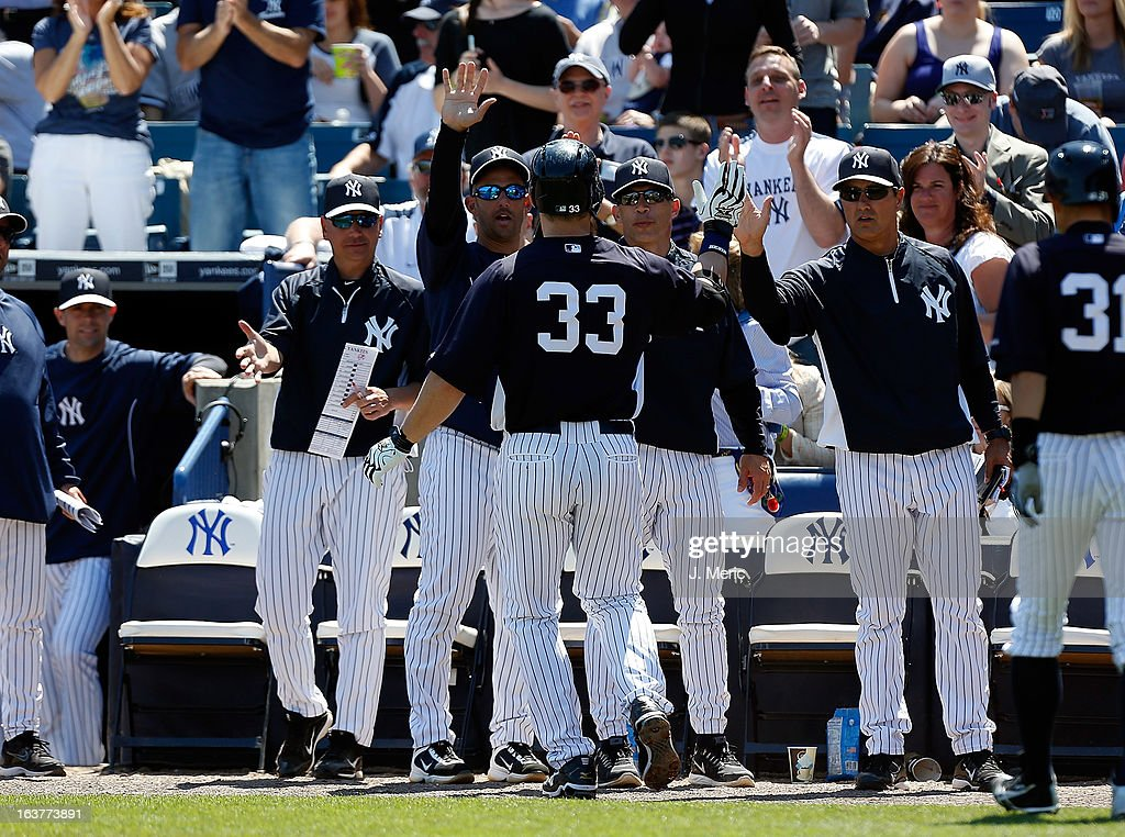 Designated hitter Travis Hafner #33 of the New York Yankees is congratulated after his home run against the Miami Marlins during a Grapefruit League Spring Training Game at George M. Steinbrenner Field on March 15, 2013 in Tampa, Florida.