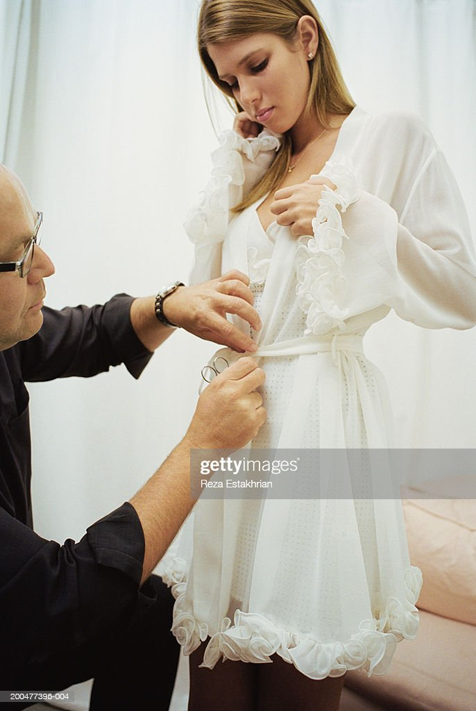 Designer adjusting lingerie on young woman : Stock Photo