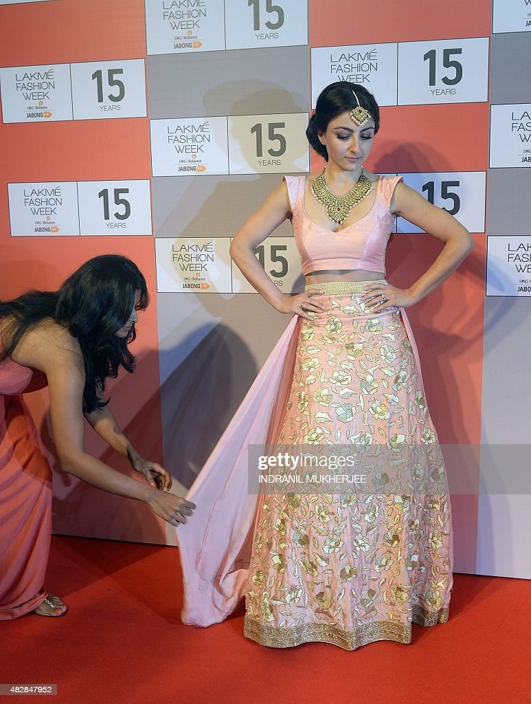A designer adjusts Bollywood actress Soha Ali Khan's dress as she poses during a curtain raiser press conference for the upcoming Lakme Fashion Week...