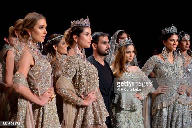 Designer Ahmad Sultan stands among models presenting his the creation during the second day of the Pakistan Fashion Design Council LOreal Paris...