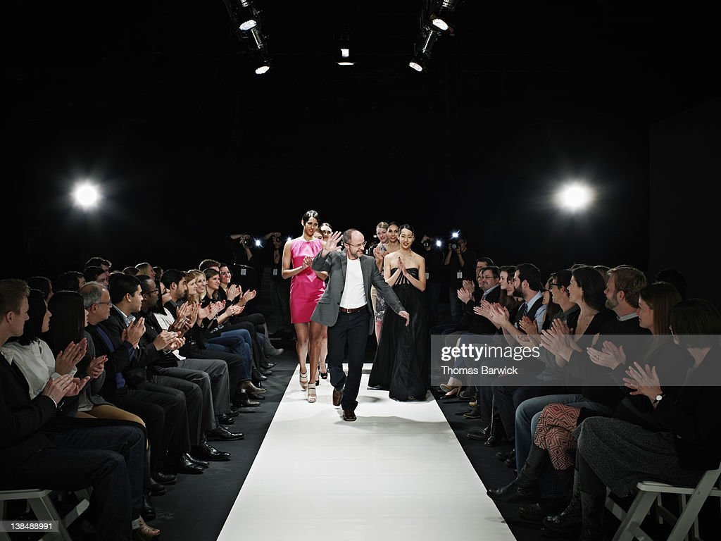 Designer and models walking down catwalk : Stock Photo