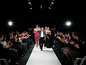 Designer and models walking down catwalk