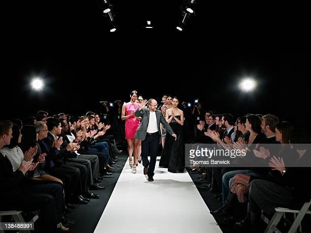 Designer and models walking down catwalk