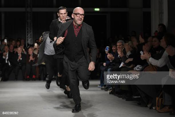 Designer Antonio Marras runs to greet the audience at the end of his show during the Women's Fall/Winter 2017/2018 fashion week in Milan on February...