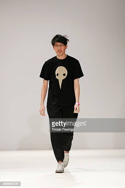 Designer Apu Jan acknowledges the crowd as he walks the runway at the Apu Jan show at the Fashion Scout venue during London Fashion Week AW14 at...