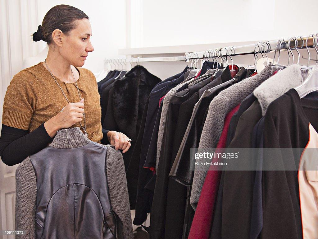 Designer arranges garments on rack : Stock Photo