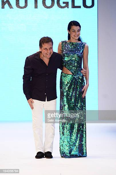 Designer Atil Kutoglu poses with a model on the runway during the Deniz Kaprol Spring / Summer 2013 show as part of Istanbul Fashion Week on October...