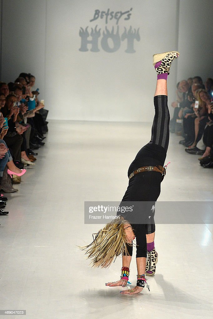 Designer Betsey Johnson cartwheels down the runway at the Marist College Presents Betsey Johnson Reprise fashion show during Mercedes-Benz Fashion Week Fall 2014 at The Salon at Lincoln Center on February 12, 2014 in New York City.