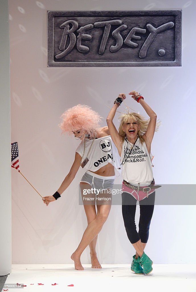 Designer Betsey Johnson walks with a model on the runway at the Betsey Johnson fashion show during Mercedes-Benz Fashion Week Spring 2014 at The Studio at Lincoln Center on September 11, 2013 in New York City.