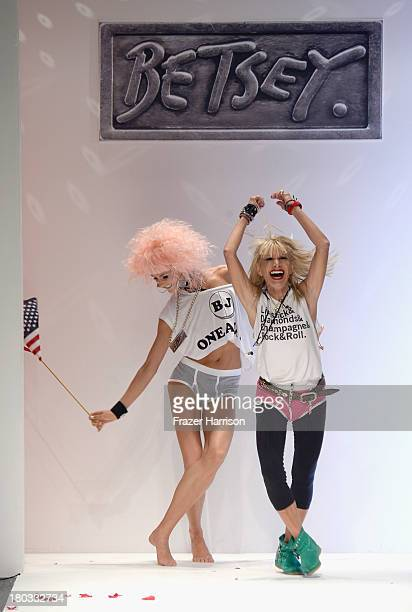 Designer Betsey Johnson walks with a model on the runway at the Betsey Johnson fashion show during MercedesBenz Fashion Week Spring 2014 at The...