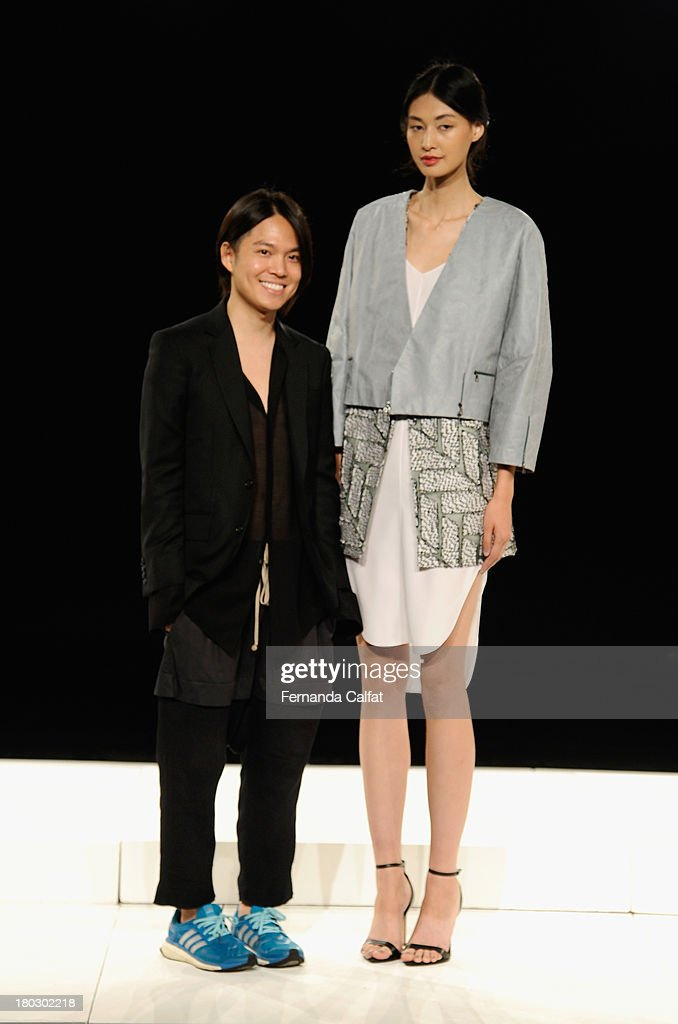 Designer Brandon Sun and a model pose at the Brandon Sun fashion presentation during Mercedes-Benz Fashion Week Spring 2014 at The Box at Lincoln Center on September 11, 2013 in New York City.