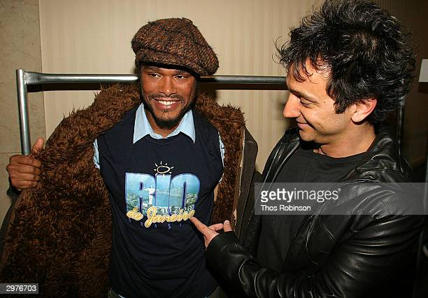 Designer Carlos Miele and singer Maxwell pose for a photo backstage after Carlos Miele's Fall 2004 fashion show during Olympus Fashion Week February...