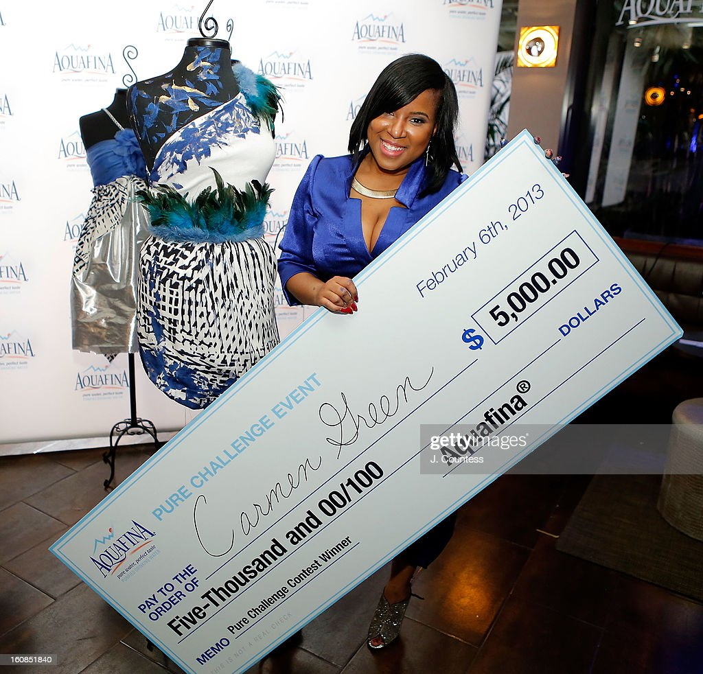 Designer Carmen Green of Baltimore, MD poses in front of her winning design with her prize check after winning The Aquafina 'Pure Challenge' at the Aquafina 'Pure Challenge' After Party at The Empire Hotel Rooftop on February 6, 2013 in New York City.