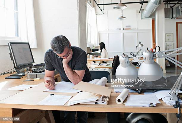 Designer checking plans and paperwork