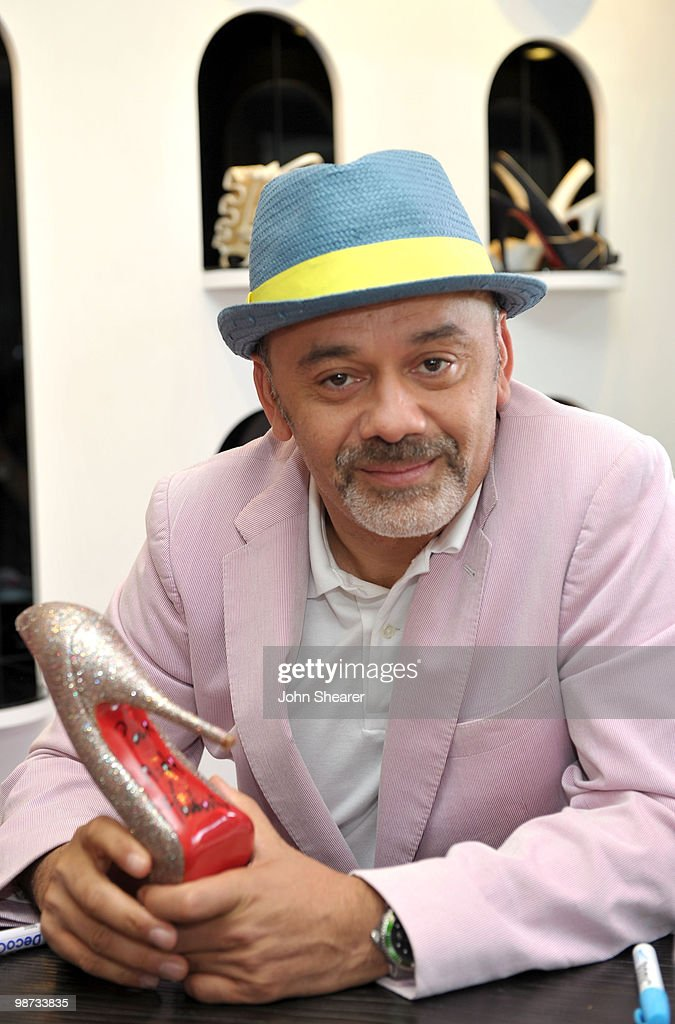 Designer Christian Louboutin signs shoes at the Christian Louboutin Boutique on April 28 2010 in West Hollywood California