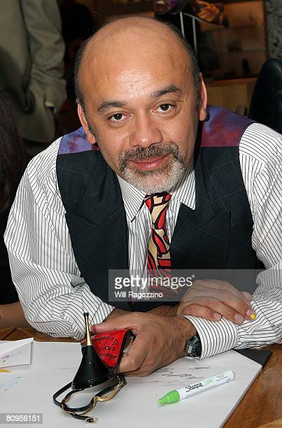 Designer Christian Louboutin signs shoes for customers at Barneys New York on May 1 2008 in New York City