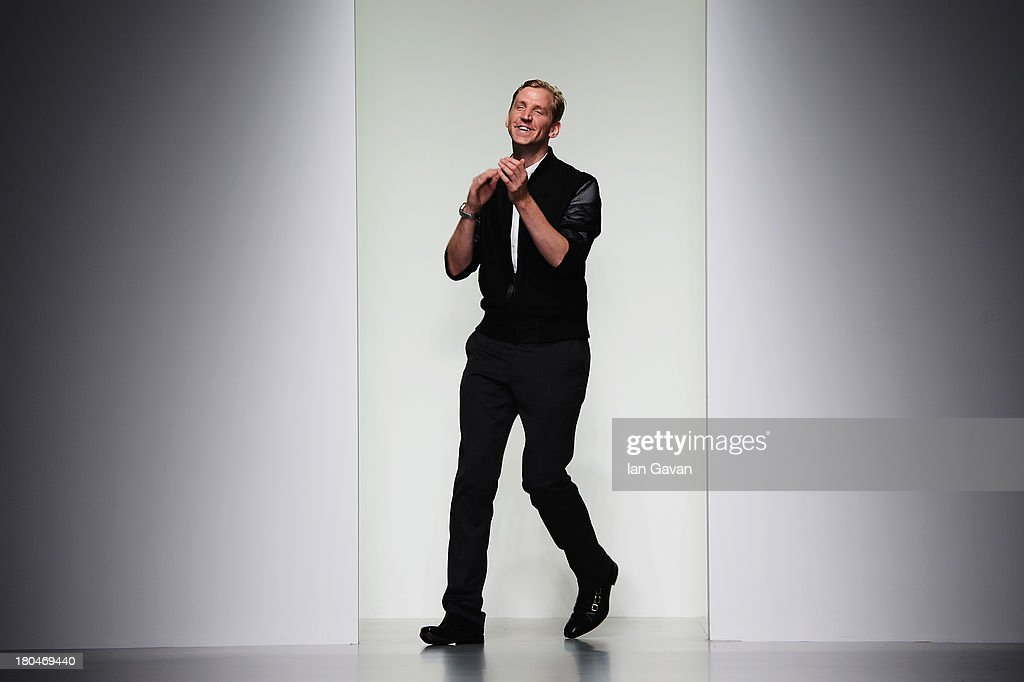 Designer Christopher Raeburn acknowledges the crowd after his show during London Fashion Week SS14 at BFC Courtyard Showspace on September 13, 2013 in London, England.
