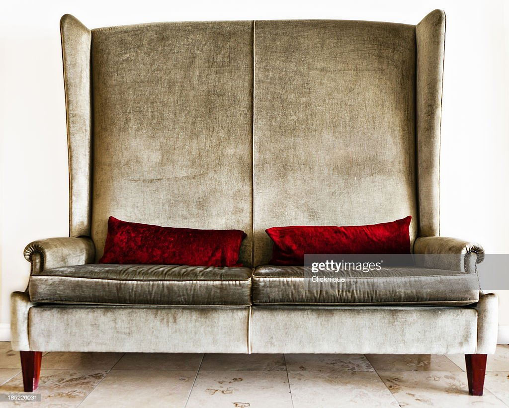 Designer couch in silver velvet with crimson pillows