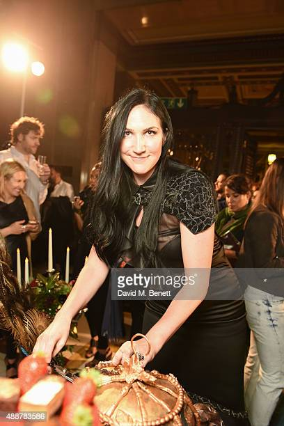 Designer Debbie Wingham serves cake to guests at the launch of new book 'Art Makeup' by Lan Nguyen Grealis at The Freemason's Hall on September 17...