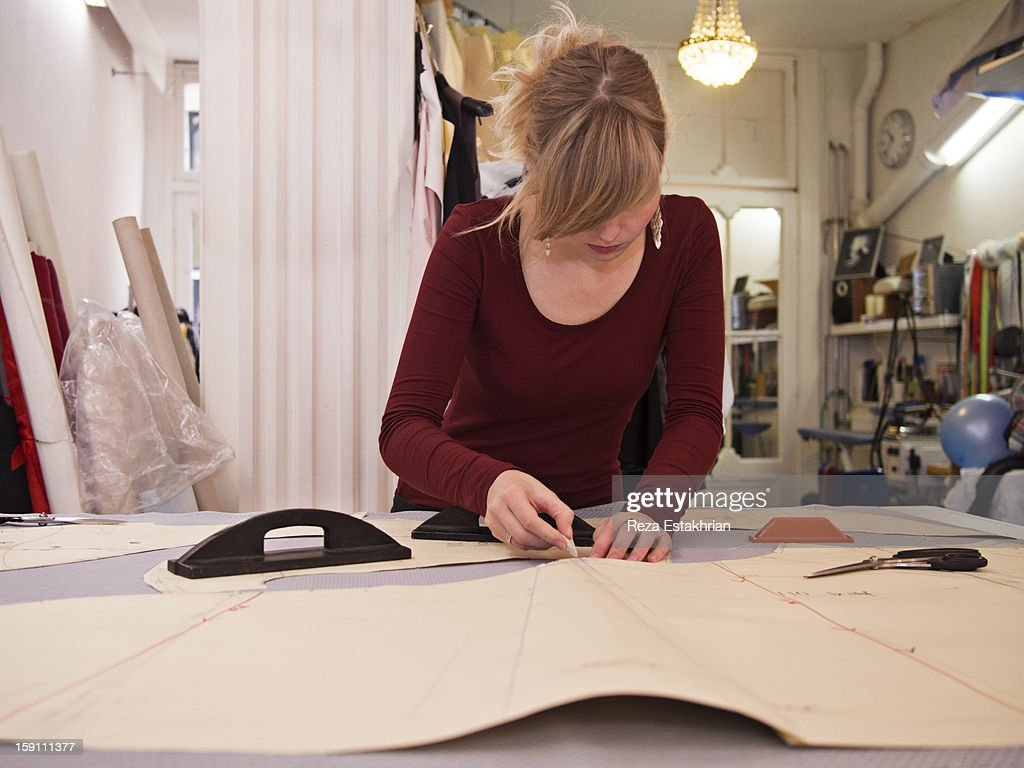 Designer draws garment pattern : Stock Photo