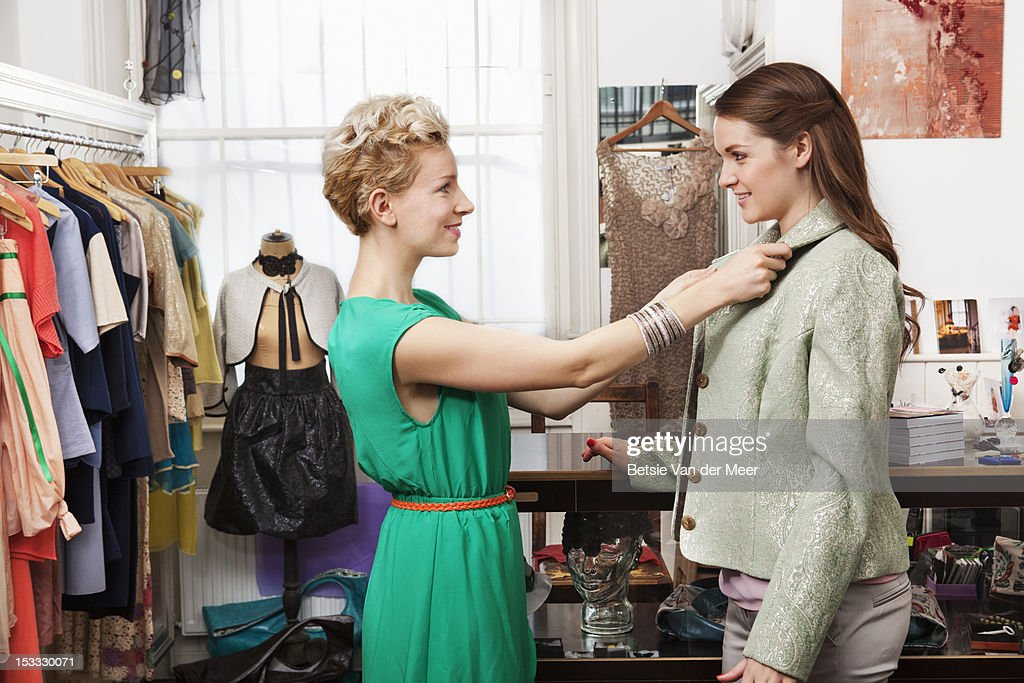 Designer dresses client in jacket. : Stock Photo
