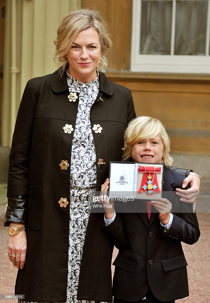 Designer Emma Hill and six year old son Hudson proudly holds his mother's Commander of the British Empire (CBE) after it was presented to her by Queen Elizabeth II, at the Investiture ceremony at Buckingham Palace on November 16, 2012 in London, England.