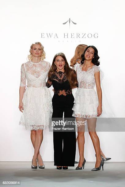 Designer Ewa Herzog acknowledges the audience with models Franziska Knuppe and Rebecca Mir after her show during the MercedesBenz Fashion Week Berlin...
