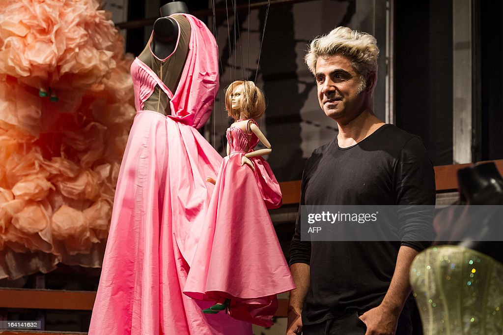 Designer Fause Haten poses next to a marionette during the Sao Paulo Fashion Week 2013 Summer collections, in Sao Paulo, Brazil, on March 20, 2013. Real size collections are also showed after the show. AFP PHOTO / Yasuyoshi CHIBA
