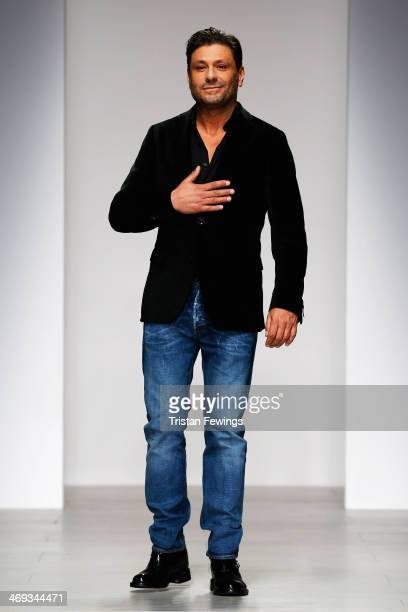 Designer Filippo acknowledges the crowd on the runway at the DAKS show at London Fashion Week AW14 at Somerset House on February 14 2014 in London...