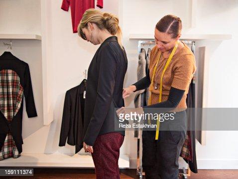 Designer fits garment on customer : Photo