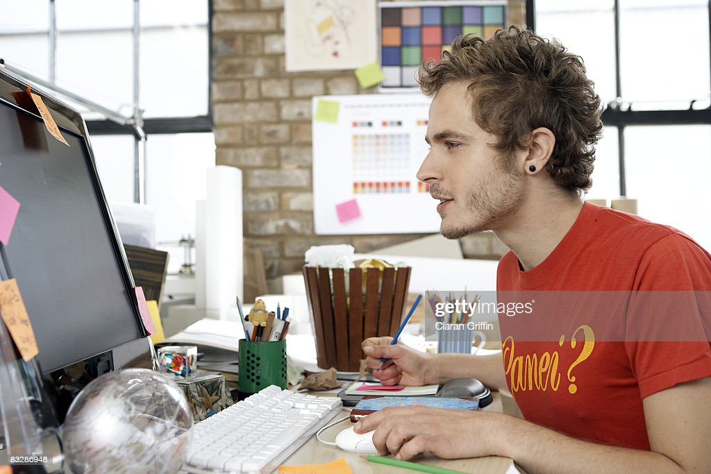 Designer focusing on his work on the computer : Stock Photo