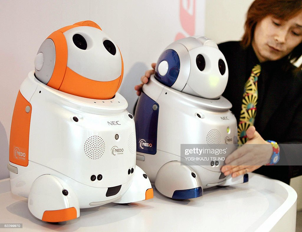 Designer for Japanese computer giant NEC Junichi Osada 'chats' with the company's childcare robot 'Papero' at a press preview for the 2005 World Expo...