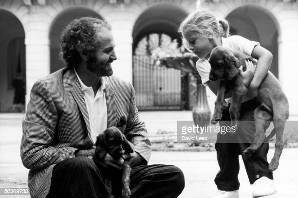 Designer Gianni Versace playing with niece Francesca and puppies