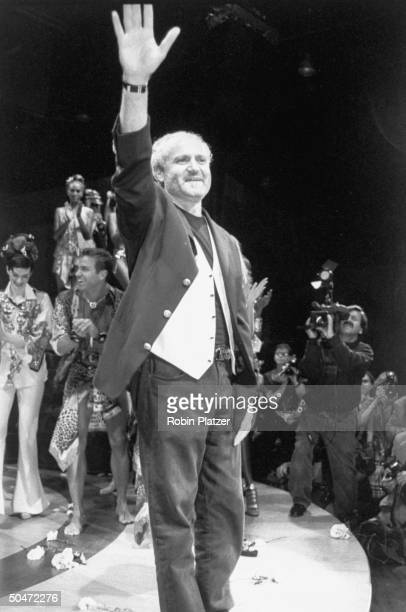 Designer Gianni Versace waving at the benefit he threw for AMFAR