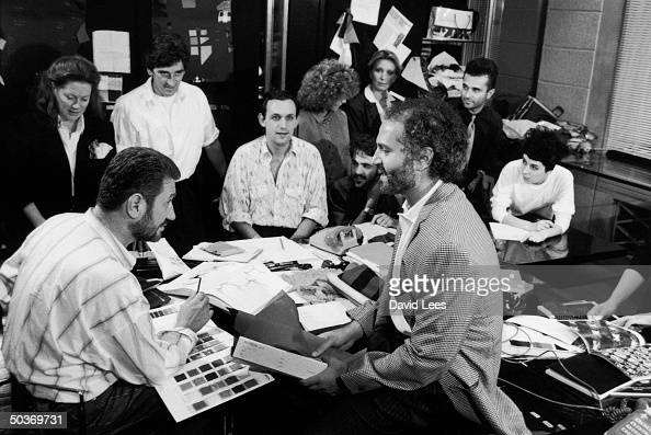Designer Gianni Versace working with his studio staff