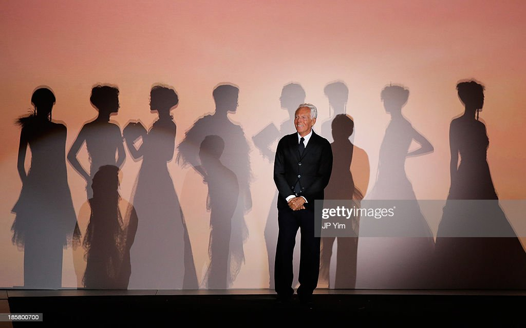 Designer Giorgio Armani acknowledges the audience after his runway show at the Giorgio Armani One Night Only NYC at Hudson's River Park SuperPier on October 24, 2013 in New York City. Armani presented his most recent Prive collection, Nude, as well as a retrospective of his couture designs alongside his 'Eccentrico' exhibition.