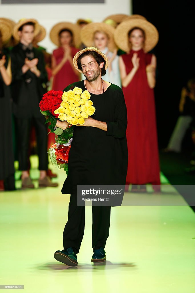Designer Goga Nikabadze salutes the crowd from the runway of the GOGA NIKABADZE show during Mercedes-Benz Fashion Week Russia S/S 2014 on October 27, 2013 in M