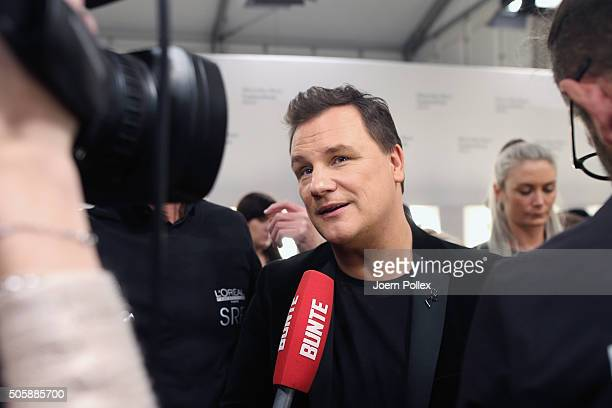 Designer Guido Maria Kretschmer is interviewed before his show during the MercedesBenz Fashion Week Berlin Autumn/Winter 2016 at Brandenburg Gate on...