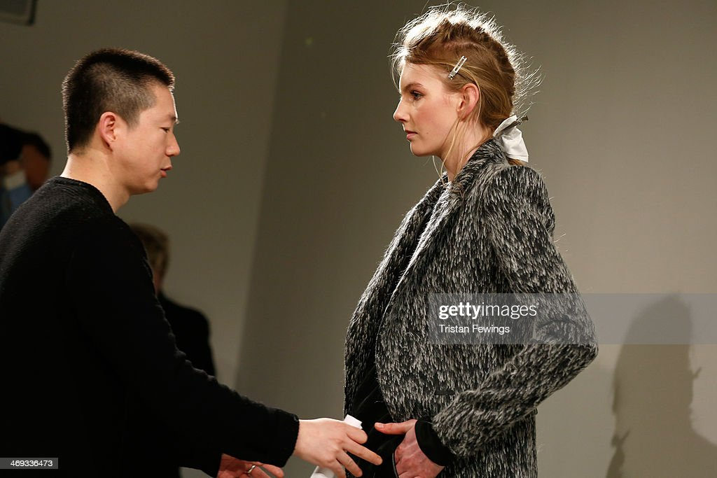 Designer Haizhen Wang directs a model prior to the Haizhen Wang presentation at London Fashion Week AW14 at Somerset House on February 14 2014 in...