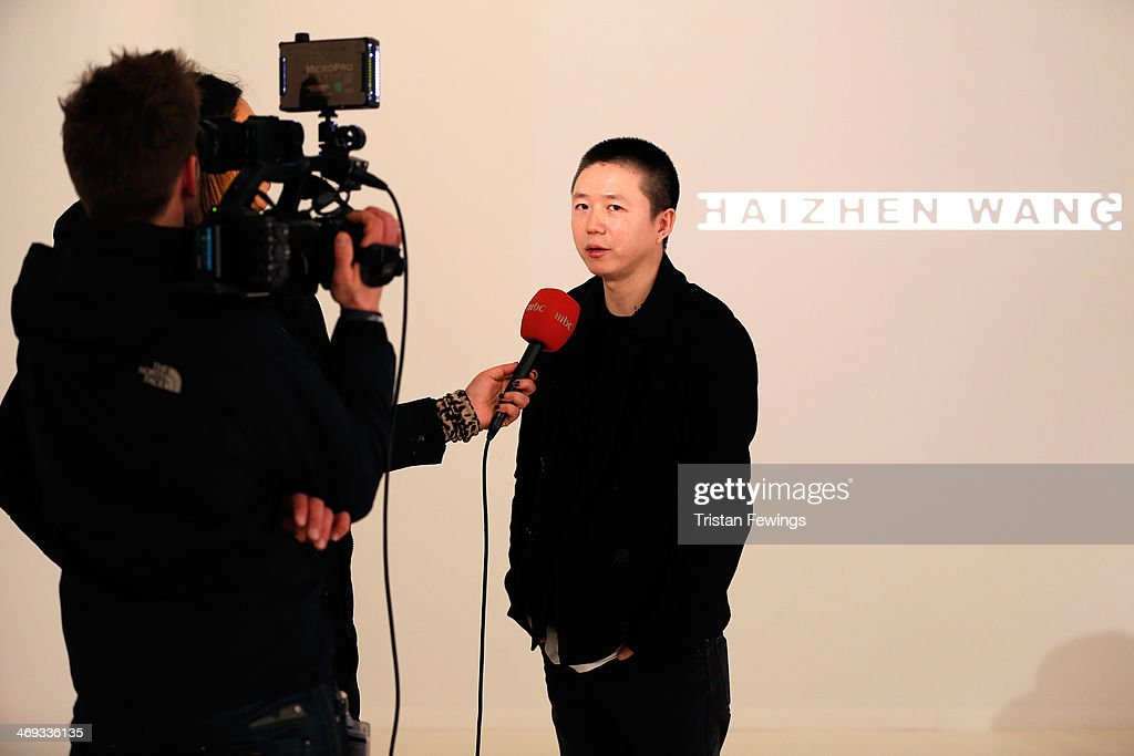 Designer Haizhen Wang talks to a reporter during the Haizhen Wang presentation at London Fashion Week AW14 at Somerset House on February 14 2014 in...