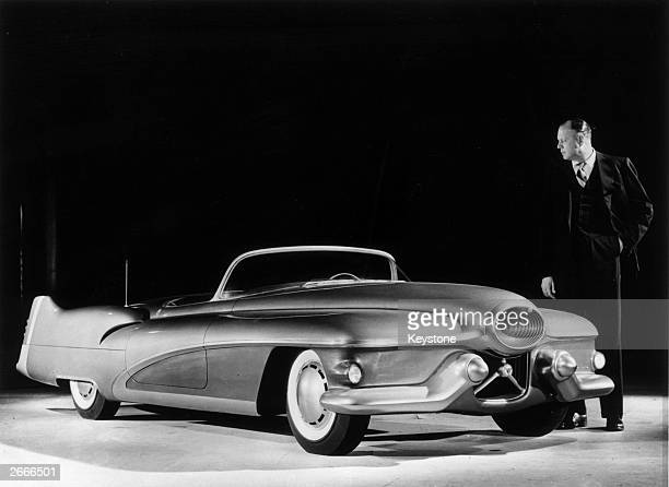 Designer Harley J Earl of General Motors examining a full scale model of the Buick Le Sabre a custom made sports car which will be used to test...