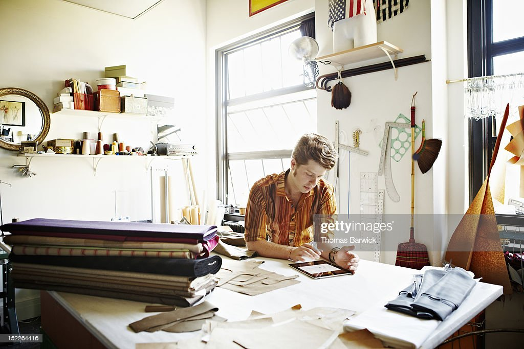 Designer in studio studying data on digital tablet : Stock Photo