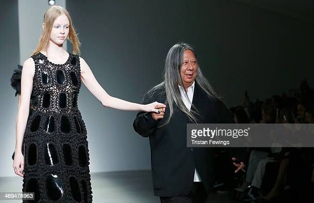 Designer John Rocha walks alongside a model on the runway of the John Rocha show during London Fashion Week AW14 at Somerset House on February 15...