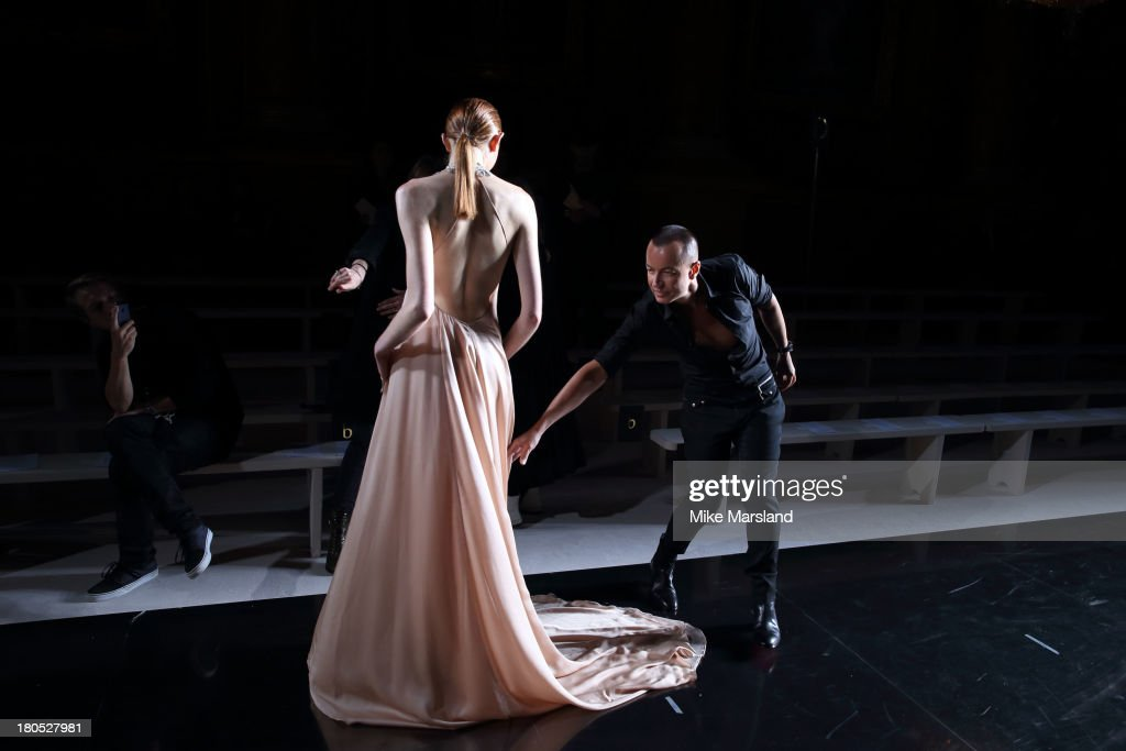 Designer Julien Macdonald makes a last minute adjustment to a model before she walks the runway at the Julien Macdonald show during London Fashion Week SS14 on September 14, 2013 in London, England.