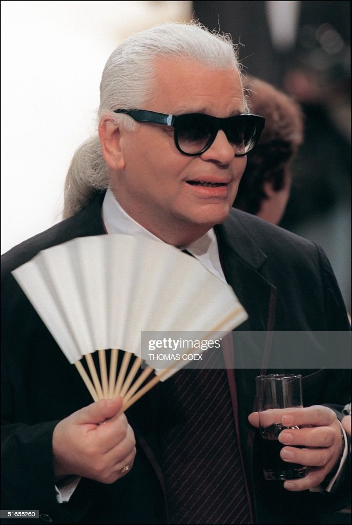 Designer Karl Lagerfeld fans himself during his show for Chanel, at the Autumn-Winter 1999/2000 haute couture collections in Paris 20 July 1999.