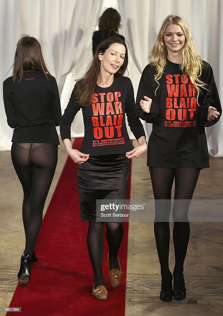 designer Katharine Hamnett (C) models her outfit with 'Stop War Blair Out' written on it and is applauded by model Jodie Kidd (R) after the Katharine Hamnett Autumn/Winter 2003 show February 18, 2003 in London.